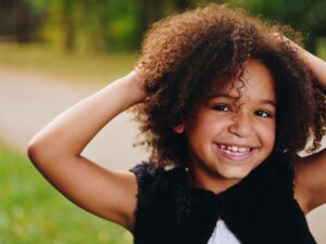 Young girl with curly hair and a blue shirt smiles for the camera.